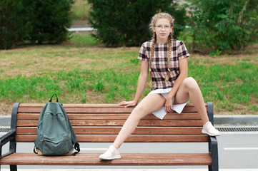 sexy nerd girl in defiant pose sitting on bench