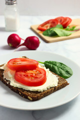 Dense rye bread with creamy cheese and tomato slices