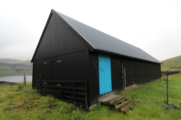 Black barn with blue door; wideangle view; faroe islands