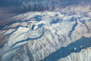 View of snowy high mountain from airplane