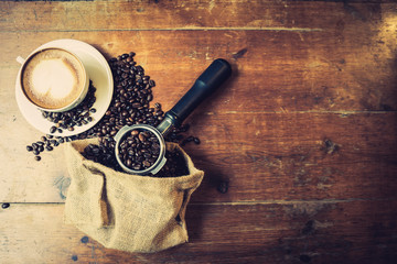 Coffee beans spilling from a burlap bag and a scoop with latte coffee on wooden background