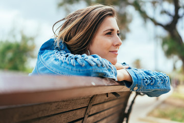 Young woman sitting on a bench daydreaming