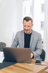 Mature man wearing grey jacket working with laptop