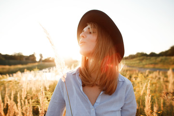 beautiful girl at the field in sunset in the hat