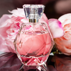 Perfume bottle with flowers on dark background. Perfumery, cosmetics, fragrance collection