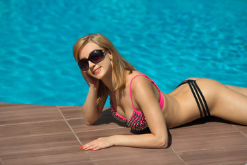 beautiful young girl in a swimsuit sunbathing by the pool in summer