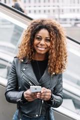 Cheerful black woman using mobile phone