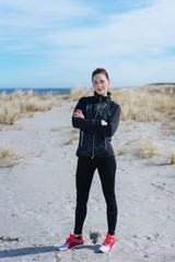 Athletic young woman standing on sand dunes
