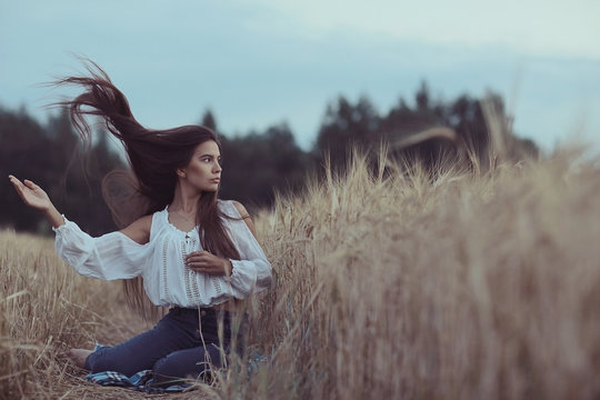 Young glamorous model posing in a field wheat