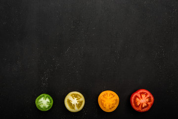 Background of sliced colored tomatoes. Fresh autumn vegetables, copy space