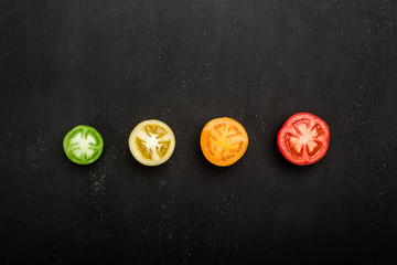 Red, green, orange and yellow tomatoes, top view. Texture of food, cut of tomato closeup.Top view with copy space