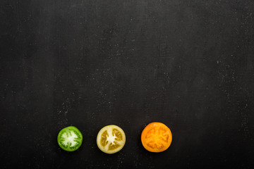 Three halves of a green, yellow, orange tomato lie on a black background. Top view, flat lay