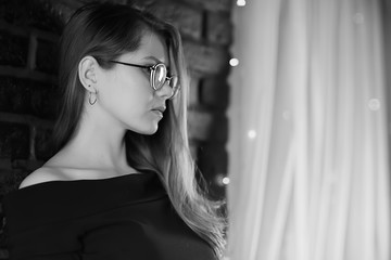 black and white photo of a girl in glasses / classic glasses girl portrait of a strict businesswoman concept