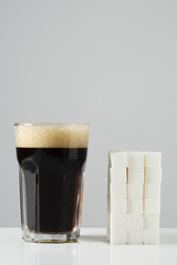 cola drink and pile of sugar cubes