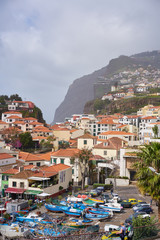 View of Câmara de Lobos in Madeira with Cape Girão on the background and boats at the marina