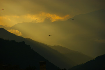 clouds with sunbeams. silhouettes of mountains and clouds at dawn