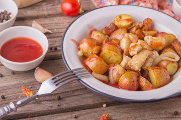 Traditional farmers food. Roasted red potatoes with carrots, onions and chicken breast pieces in old metal plate on wooden background. Served with red tomatoes and a mug of clean water. Tasty meal