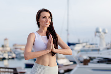 Relaxing woman practices yoga at dawn, doing tree pose at marine dock, being happy with life, beautiful body, ideal yoga.