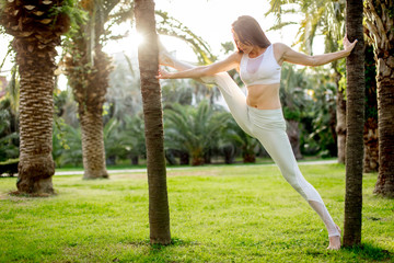 Athletic girl in wite sportswear engaging in Rhythmic Gymnastics in outdoor, stretching legs, leaning raised foot on palm tree. Healthy lifestyle, Outdoor Activity, Sport Apparel