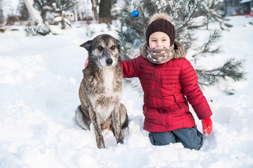 Little girl plays with her dog in snow.