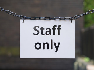 """Close-up of white board with black texts """"Staff only"""" hanging from metal chains closeing the public access. Outdoor, sunny day."""