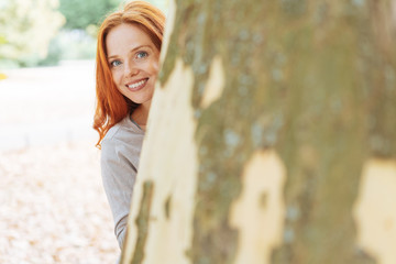 Cute young woman peering around a tree trunk