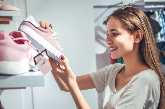 happy young woman customer choosing pair of sneakers shoes