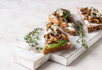 Whole grain rye bread toast with cream cheese or ricotta, mushroom and herbs on a white wooden cutting board.