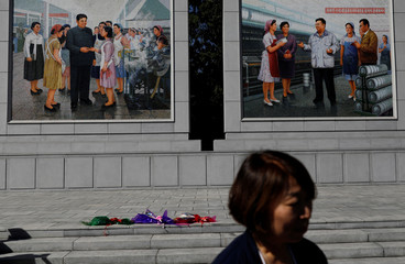 An overseas North Korean citizen leaves flowers in mark of respect in front of paintings featuring late North Korean leaders Kim Il-sung and Kim Jong-il at a silk factory during a government organised visit for foreign reporters in Pyongyang