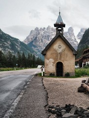 A picturesque panorama in the Dolomites. There are huge mountains covered with snow, coniferous forests, mountain clear azure lake, a lonely wild place, a deserted Church on the road