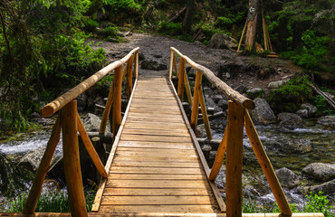 Wooden bridge over a mountain river. Close-up.