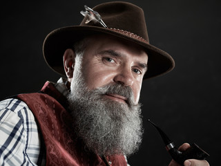 dramatic portrait of gray bearded smiling senior man in hat smoking tobacco pipe. view of Austrian, Tyrolean, Bavarian old man in national traditional costume in retro style.