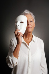 serious looking mature woman revealing true face behind mask