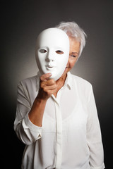 happy smiling playful mature woman peeking from behind mask