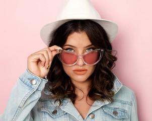 Young woman wearing denim jacket and hat studio shot