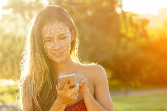 model woman long-haired in red dress holds phone and talking typing text with boyfriends in hand rays of sun background . enamored girl chating with friends in the park, concept face id