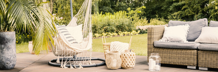 Lanterns and basket between rattan sofa and hammock with pillows in the garden. Real photo