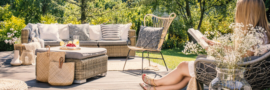 Woman reading book on patio with rattan table, chair and sofa in the garden during summer. Real photo