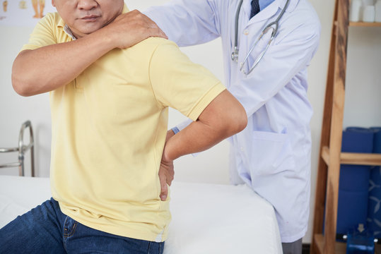 Crop medical practitioner examining sore back of adult man while working in hospital