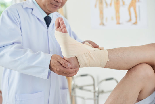 Unrecognizable adult doctor wrapping clean bandage carefully around foot and ankle of crop man while working in office