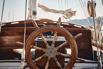Closeup of a vintage hand wheel on a wooden sailing yacht.