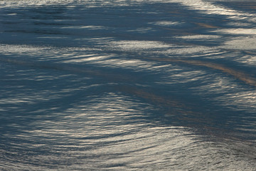 Wall Mural - Calm water surface as background. Quiet waves create colorfulness by reflection of the sunset sky.