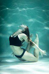 Woman under the water in a black clothes.