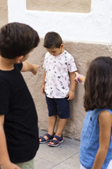 Two kids making bullying to another boy.