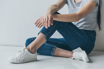 cropped shot of girl in jeans sitting on floor near grey wall