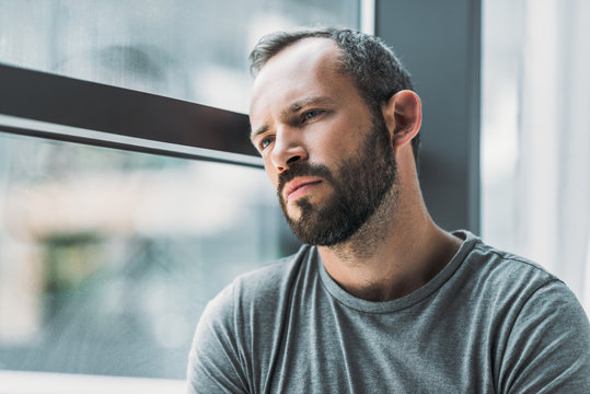 frustrated bearded man leaning at window and looking away