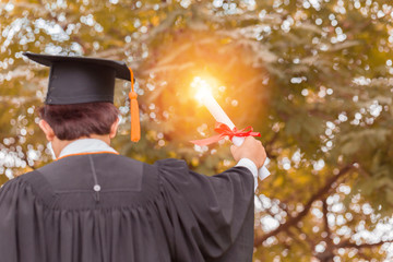 Graduate in gown put hands up and celebrating with certificate in hand and feeling so proud and happiness in Commencement day,Education Success Concept