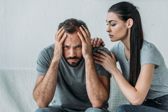 young woman supporting depressed frustrated boyfriend sitting on couch and looking at camera