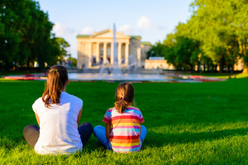 children sitting on the grass in the park in front of the Grand Theatre -  neoclassical opera house located in Poznań, Poland - in the rays of the setting sun