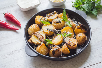 Rustic potatoes with mushrooms on a white wooden table. Top view.
